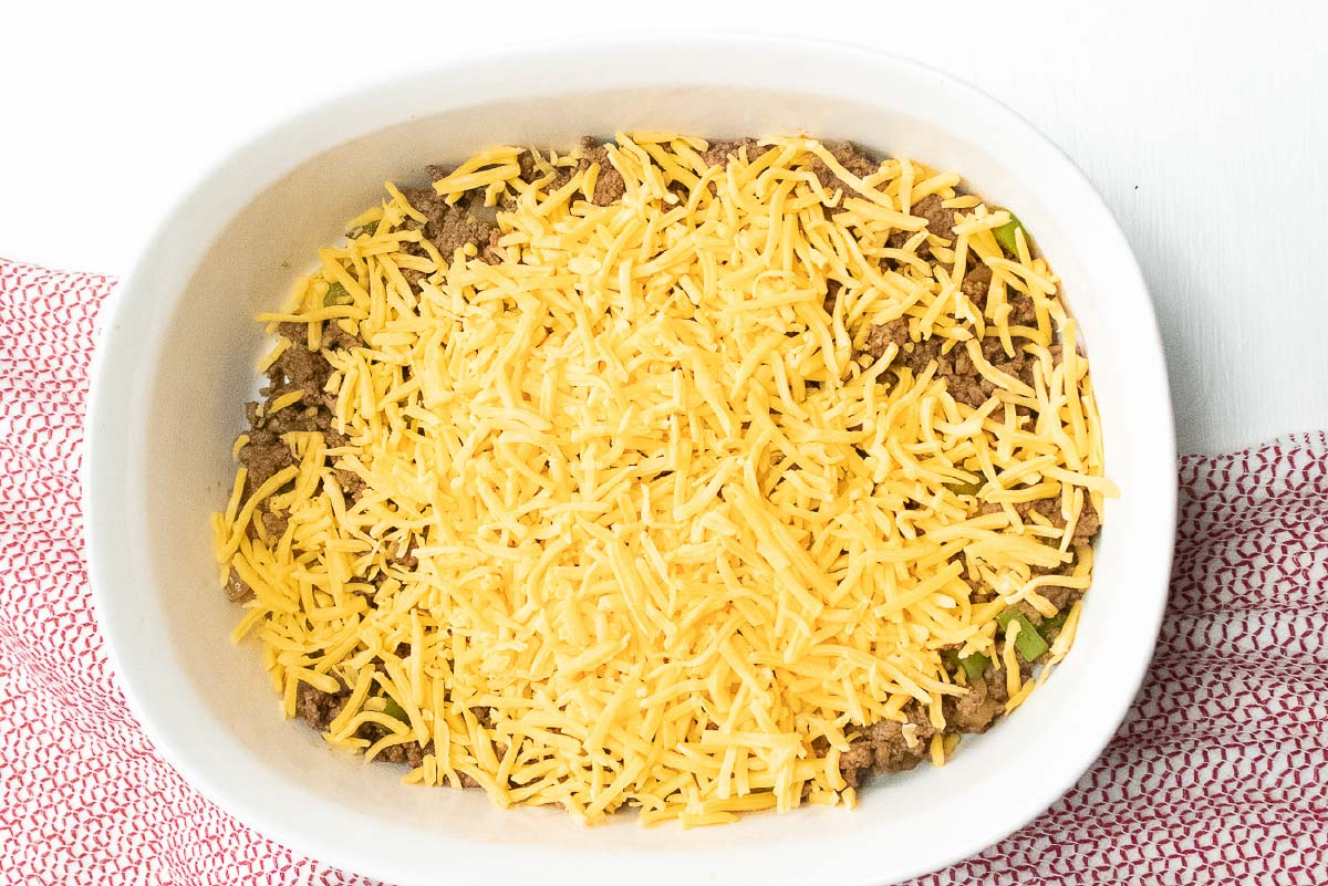 Cooked ground beef, diced onions and bell peppers in a white casserole dish, topped with shredded cheddar cheese.