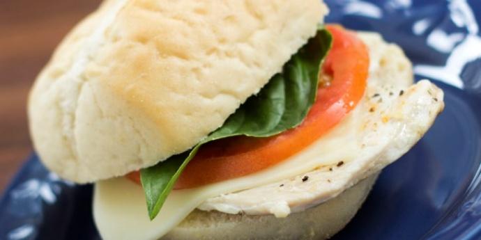Turkey slice with mozzarella cheese, tomato, and basil on a white sandwich roll