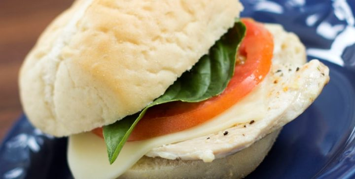 Turkey slice with mozzarella cheese, tomato, and basil on a white sandwich roll