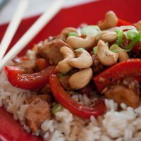 Red plate with chopsticks and rice, sliced red bell peppers, cashews, chicken, and green onions