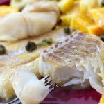 Cooked tilapia with capers and orange slices on top on a red plate with a fork