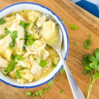 Chicken and dumplings garnished with parsley in a white bowl with a blue rim. There is a spoon with a dumpling and some broth. The bowl is on a wooden cutting board on top of a blue napkin with white stripes, all on a white marble counter.