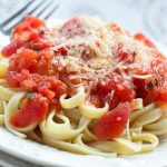 White plate with fettuccine and tomato sauce, topped with Parmesan cheese