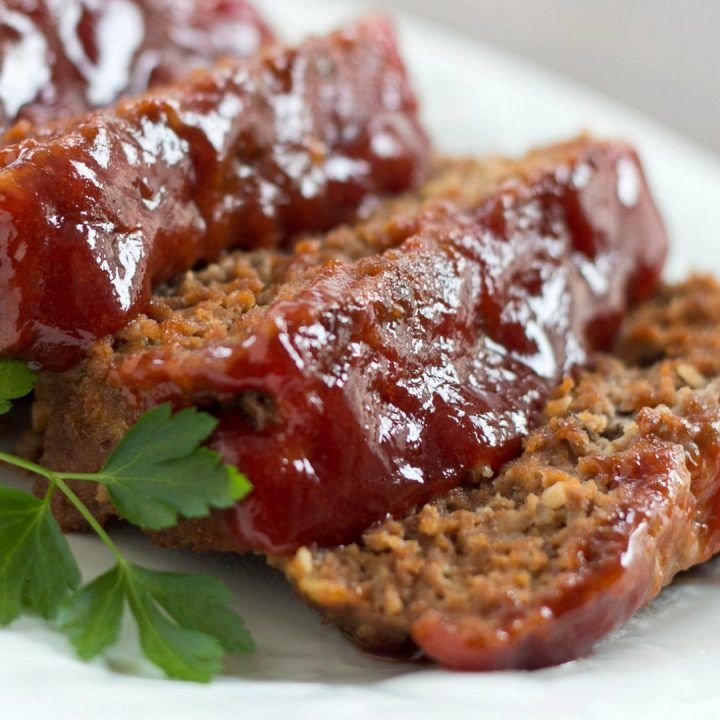 Slices of glazed meatloaf on a white plate.