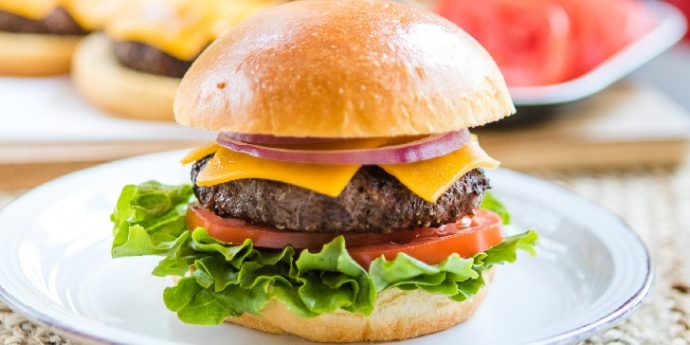 Lettuce, tomato slice, hamburger patty with melted slice of cheddar cheese, and two rings of red onion on a hamburger bun sitting on a white plate.