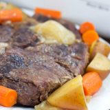 Roast beef with chopped carrots and potatoes on a white plate