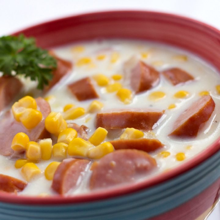 White chowder with sausage slices and corn, with a parsley garnish in a red bowl with a blue stripe