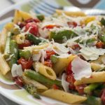 Cooked penne pasta, 1-inch pieces of asparagus, grape tomatoes, topped with a garnish of parmesan cheese on a white plate with blue and brown stripes