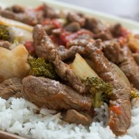 Cooked strips of beef with onions, brocolli florets, diced tomatoes, and mushrooms on a bed of rice
