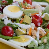 Cobb salad on a white square plate on a yellow tablecloth. Cobb salad ingredients are lettuce, grape tomatoes, sliced boiled eggs, diced avocado, diced chicken, shredded carrots, and blue cheese dressing.
