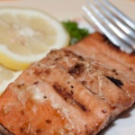 Pieces of cooked salmon on a white plate with a fork, garnished with two lemon slices and parsley