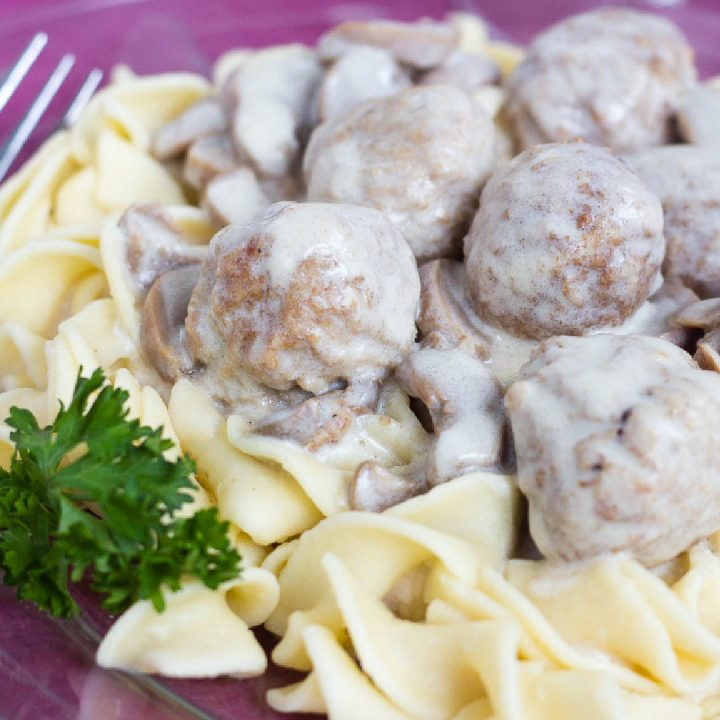 Wide egg noodles and meatballs topped with a mushroom sauce on a purple plate with a fork, garnished with parsley