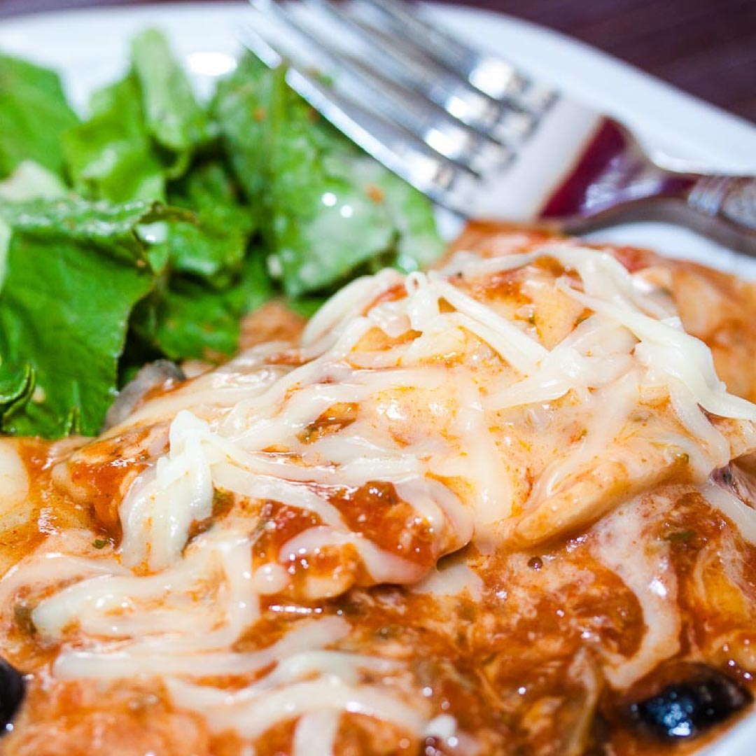 A plate of ravioli covered with melted cheese and marinara sauce and a black olive, garnished with a sprig of parsley, with a tossed salad and a fork in the background