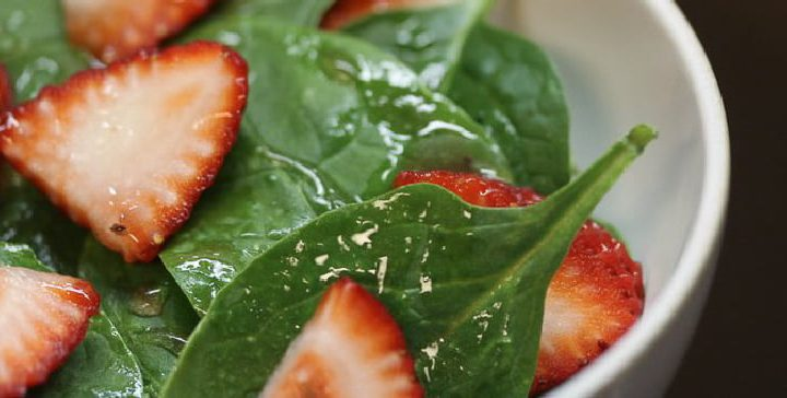 spinach leaves and sliced strawberrys tossed with dressing in a white bowl