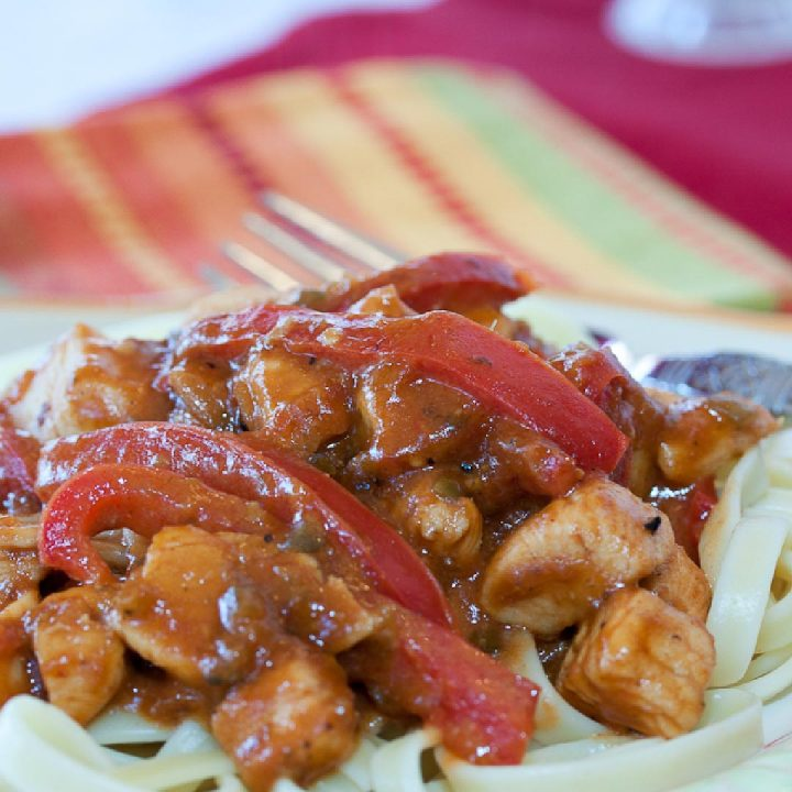 White plate with brown rim and fork with diced chicken, fettuccine, and sliced red bell pepper in a peanut sauce with red, yellow, green, and orange striped cloth napkin in background