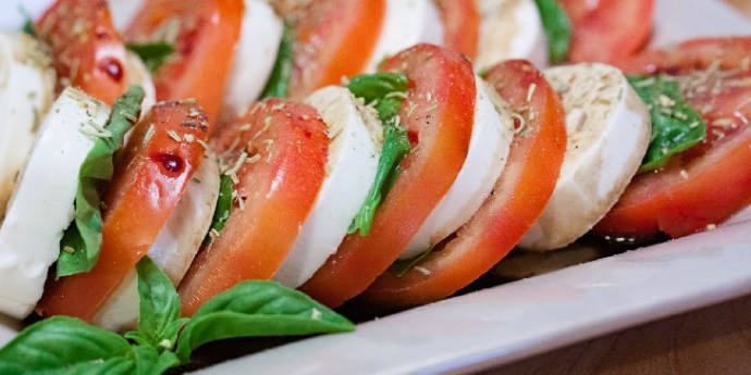 Photo is caprese salad on a white plate, with balsamic vinegar in the bottom of the plate. On the plate is alternating slices of fresh mozzarella cheese and fresh tomotoes, interspersed with fresh basil. There is Italian seasoning sprinkled on the cheese and tomatoes.
