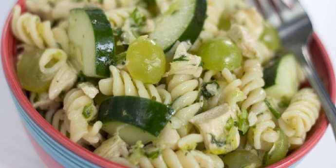 Bowl full of spiral pasta, diced chicken, grapes cut in half, and cucumber slices. There is a fork in the bowl.