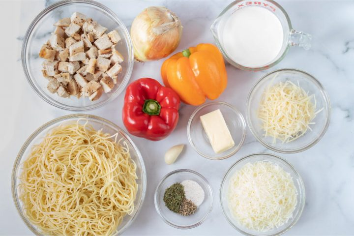 The ingredients for this recipe. A bowl of angel hair pasta, a bowl of diced cooked chicken, one onion, one red bell pepper, one yellow bell pepper, one clove of garlic, one bowl with salt and pepper, one bowl with a partial stick of butter, one measuring cup of half and half, one bowl of shredded parmesan cheese, and one bowl of shredded mozzarella cheese, all on a white marble counter.