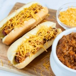 Two hot dogs in buns topped with chili and shredded cheese, a bowl of shredded cheese, and a bowl of chili.