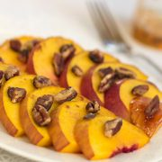 White plate with peach slices topped with chopped pecans.