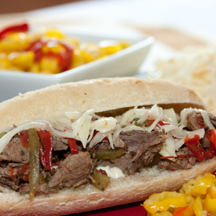 A hoagie roll on a red plate with shredded roast beef, onions, and bell peppers, with a white bowl of pickled peppers in the background.
