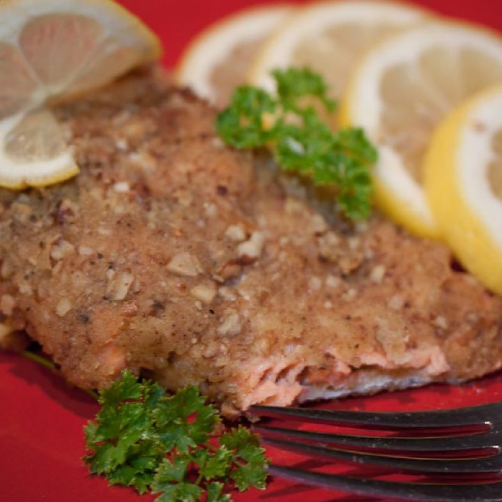 Pecan crusted salmon on a red plate with a fork, garnished with lemon slices and sprigs of parsley.