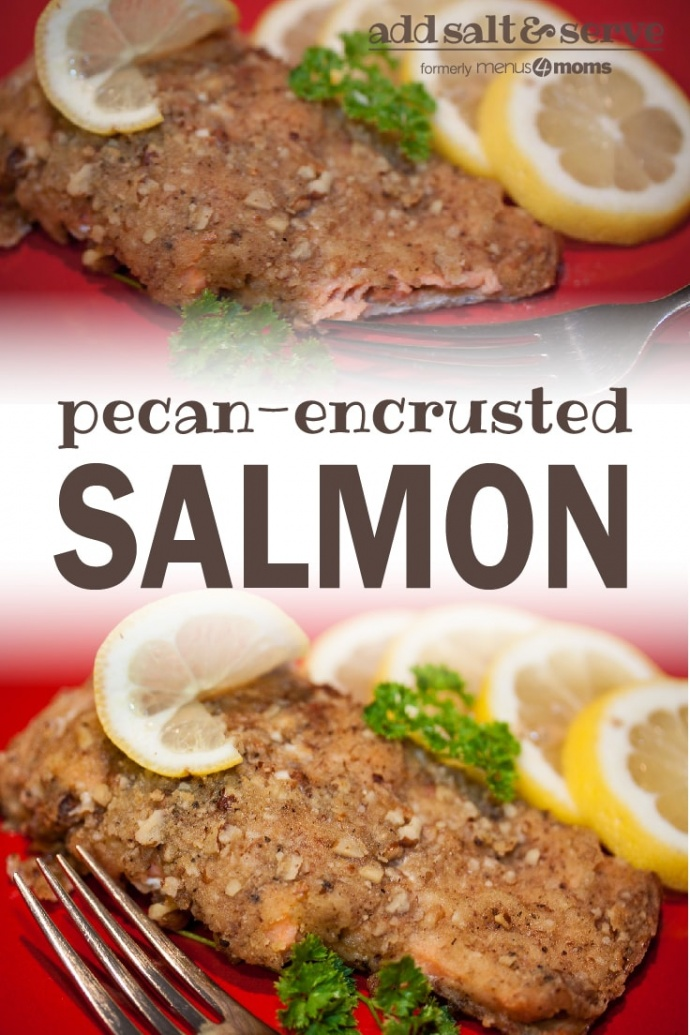 Pecan crusted salmon on a red plate with a fork, garnished with lemon slices and sprigs of parsley; text pecan-encrusted salmon add salt & serve formerly menus4moms