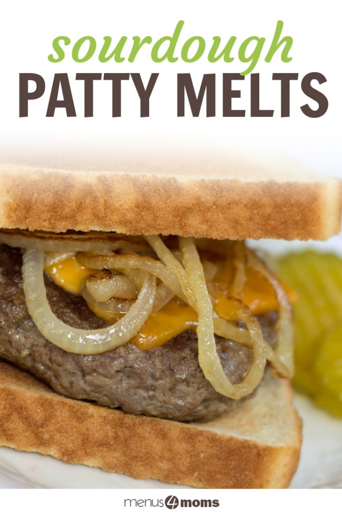 A hamburger patty topped with a slice of melted cheese and sauteed onion rings between two slices of toasted sourdough bread. The sandwich is on a white plate and garnished with pickle slices; text Sourdough Patty Melts Add Salt & Serve