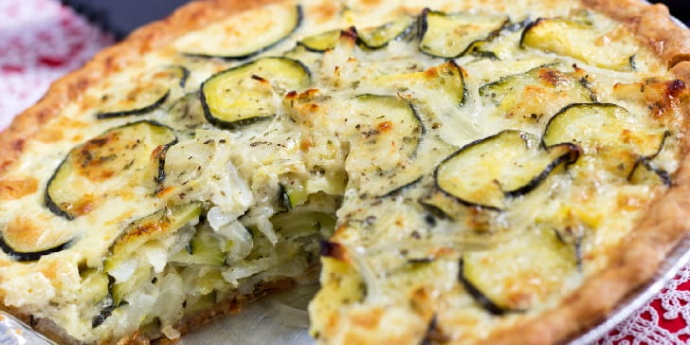 Photo is of a pie tin with a quiche with one triangular piece cut out of it. The quiche has a pie crust, sliced onions and zucchini inside, and sliced zucchini and melted mozzarella cheese on top.