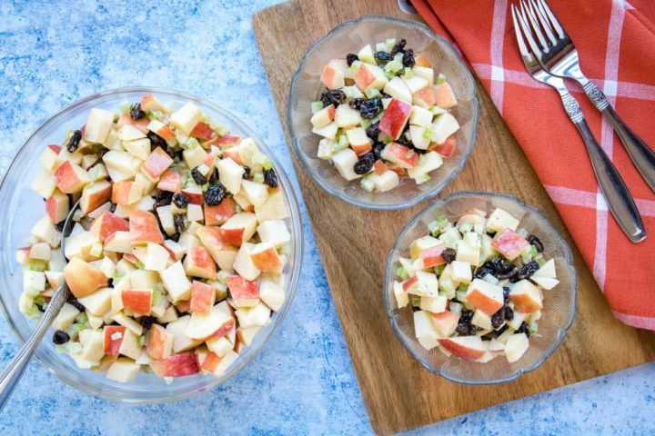 Overhead view of salad with chopped apples, raisins, and celery with a coral plaid towel and two forks.