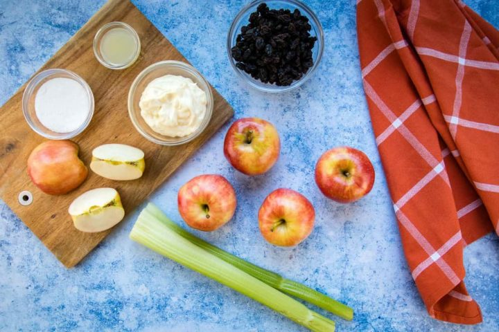 Overhead view of 4 5 apples (one chopped), two stalks of celery, a bowl of raisins, a bowl with mayonnaise, a small bowl with lemon juice, and a small bowl with sugars all on a blue surface with a coral plaid towel to the side