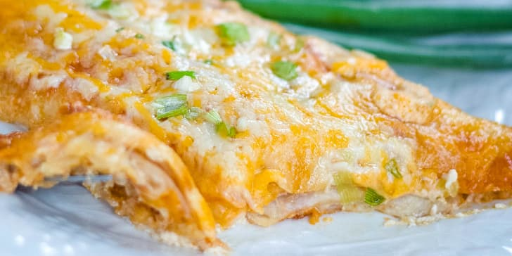 Enchilada covered with melted Mexican blend cheese and diced green onions on a clear plate with green onions in the background.