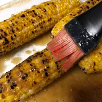 Grilled corn in a clear Pyrex dish with a silicone brush basting with garlic ginger soy butter