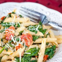 White plate with penne pasta, cooked baby spinach, cherry tomatoes, and shredded mozzarella cheese. There is a fork on the plate.