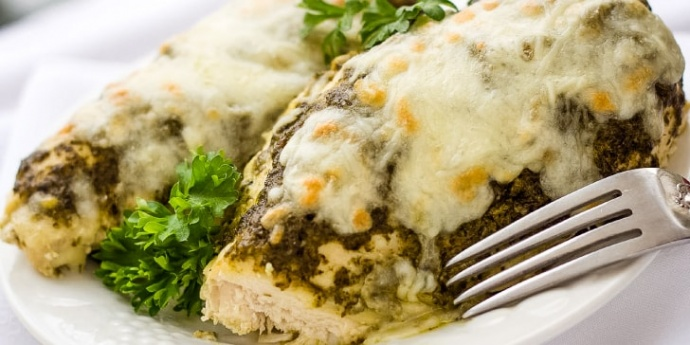 White plate with two chicken breasts topped with pesto and melted mozzarella cheese, garnished with parsley. There is a fork on the edge of the plate.