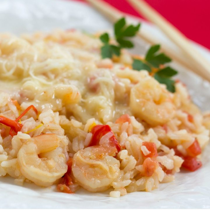 White plate with rice, shrimp, diced tomatoes, and strips of bell peppers, with melted Monterey Jack cheese on top.