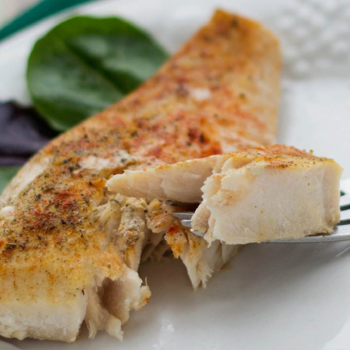 fillet of white fish seasoned with red spices with a bite on a fork