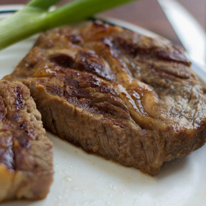 A cooked steak on a white plate with a stalk of celery in the background.