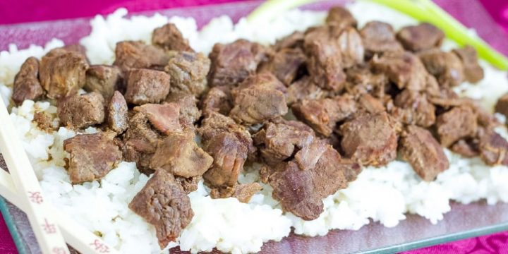 Diced steak on a bed of rice on a clear glass plate. There are chopsticks on the edge of the plate.