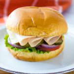 Brioche bun with slices of turkey, Swiss cheese, lettuce, tomato, pickle, and onion on a white and orange plate with coral and white windowpane towel in the background