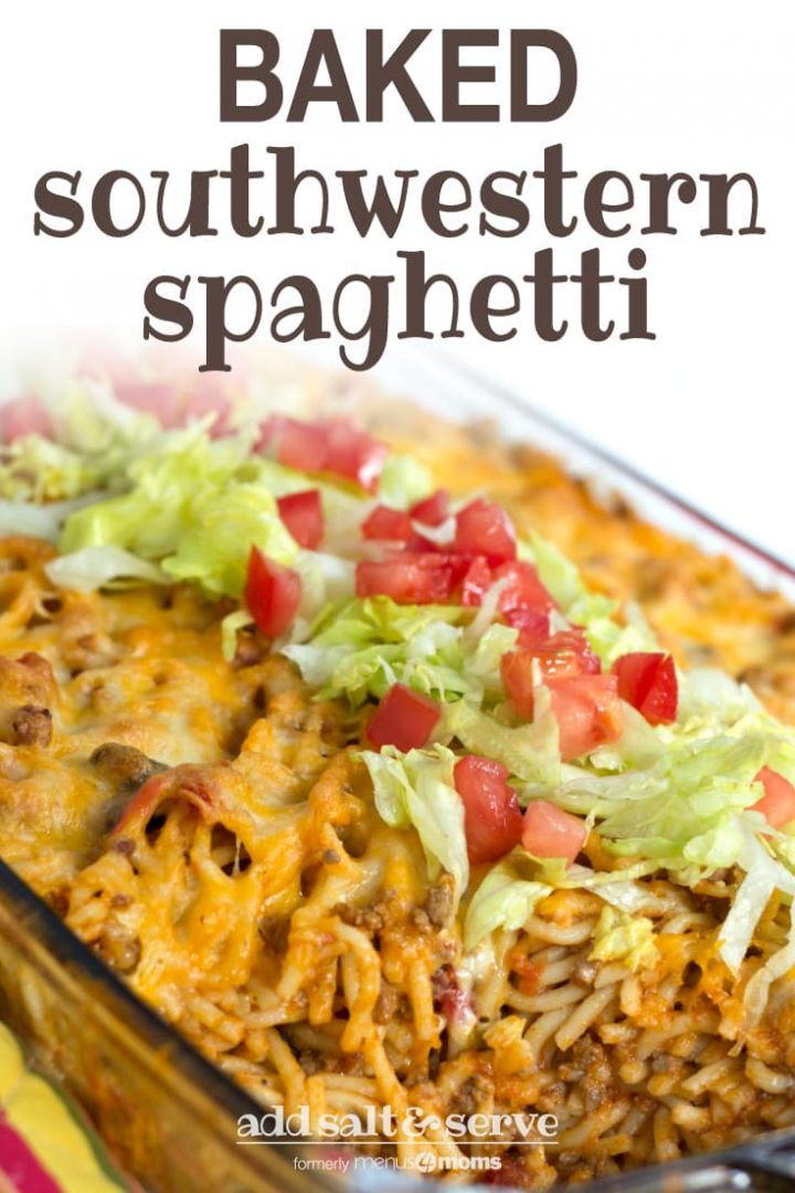 Clear casserole dish with spaghetti noodles, ground beef, and melted cheese, topped with shredded lettuce and diced tomatoes. Text baked southwestern spaghetti add salt & serve formerly menus4moms