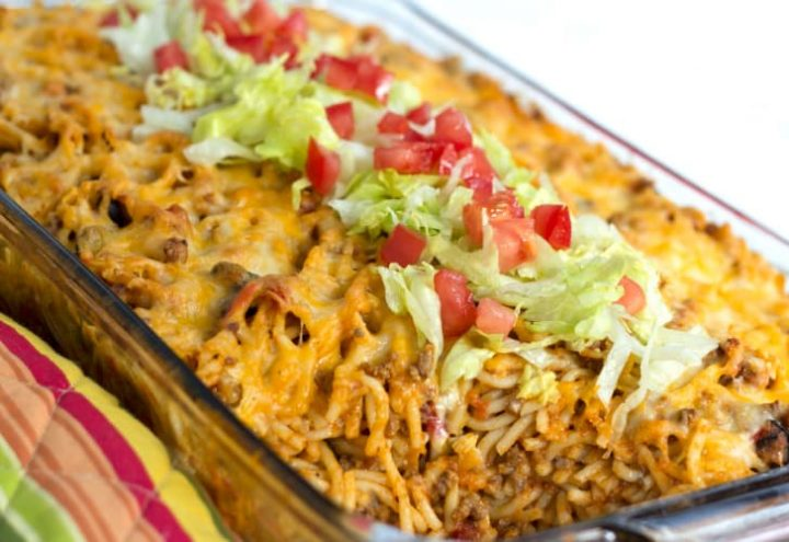 Clear casserole dish with spaghetti noodles, ground beef, and melted cheese, topped with shredded lettuce and diced tomatoes.