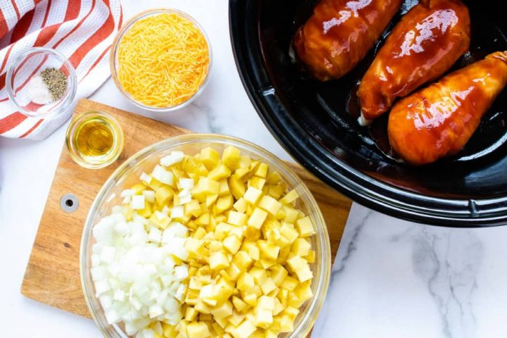 Small bowl with salt and pepper sitting on an orange and white striped napkin, a bowl of shredded cheddar cheese, a slow cooker with three chicken breasts in barbecue sauce, a wooden cutting board a bowl of diced potatoes and onion, and a small bowl with oil.