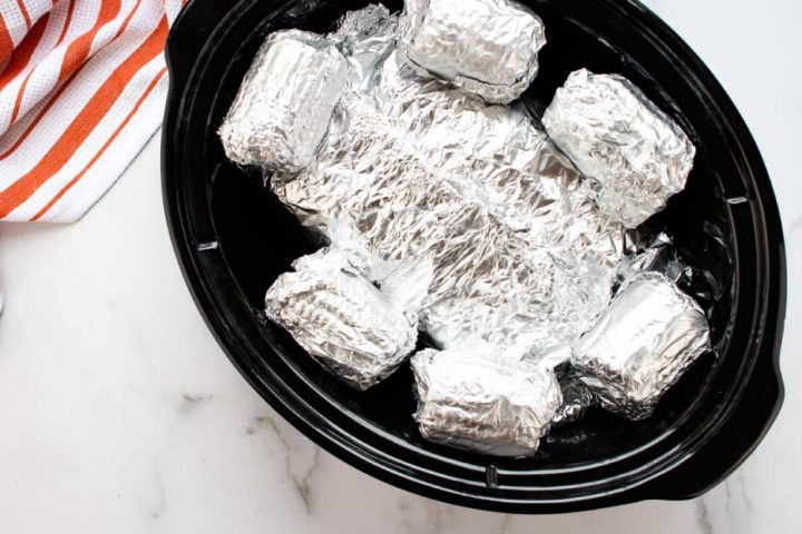 Slow cooker with six small corn cobs wrapped in foil and another foil packet beneath them.