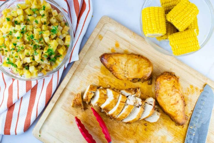A clear glass bowl with diced potatoes sitting on an orange and white striped napkin, a clear glass bowl with small corn cobs, and a wooden cutting board with two whole chicken breasts and one sliced chicken breast. There is a set of tongs and a Santoku Knife on the cutting board.