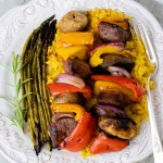 grilled kabobs of red, yellow, and orange bell pepper pieces alternated with mushrooms, red onion pieces, and marinated beef and layered over yellow rice with grilled asparagus on a white plate with a silver fork