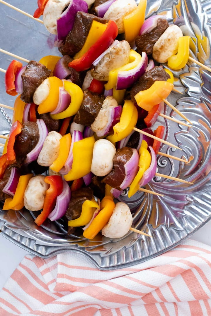uncooked kabobs of beef alternated with red, yellow, and orange bell peppers, mushrooms, and red onions on a pewter platter