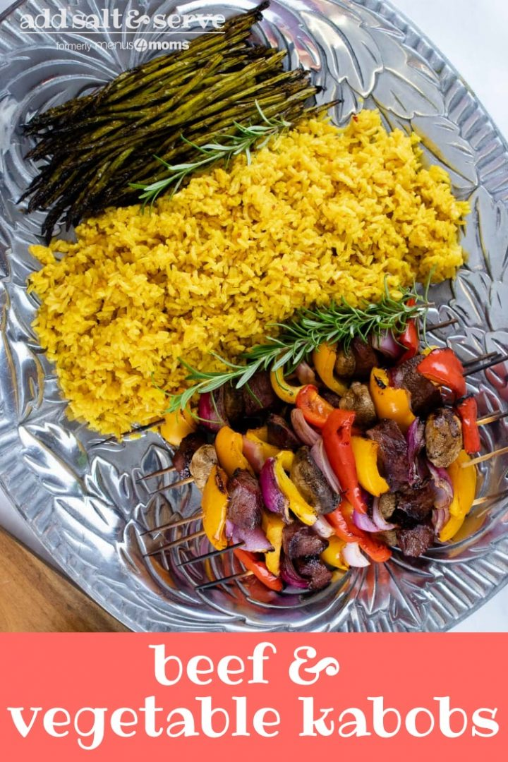 Large pewter platter of yellow rice, grilled asparagus, and grilled beef kabobs with bell peppers, red onions, and mushrooms with text Beef & vegetable kabobs Add Salt & Serve