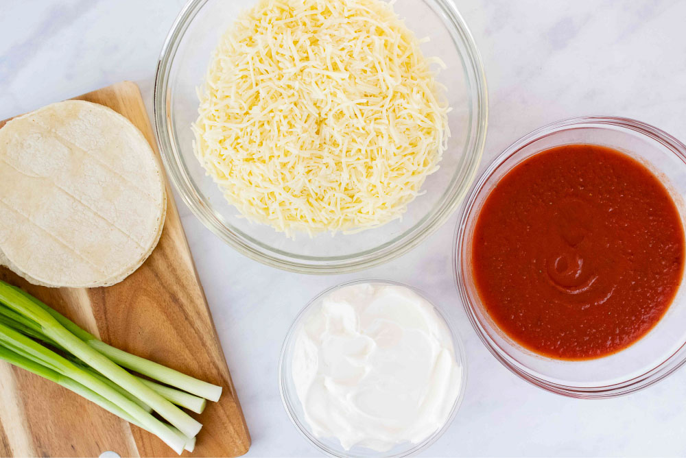 Overhead view of green onions, corn tortillas, grated quesadilla cheese, sour cream, and enchilada sauce