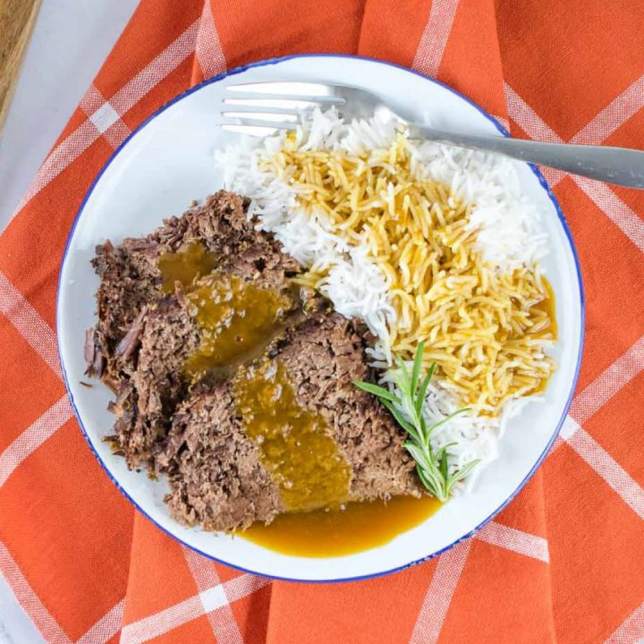 a white plate half full of roast beef and half full of rice. Roast beef and rice are both covered with gravy. There is a fork on the plate next to the rice. The plate is on an orange napkin with white stripes.